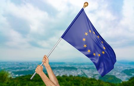 democracia: Las manos del hombre joven que agitan orgulloso la bandera de unión europea en el cielo, parte representación 3D