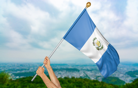 Young mans hands proudly waving the Guatemala national flag in the sky, part 3D rendering