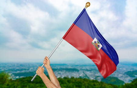 Young mans hands proudly waving the Haiti national flag in the sky, part 3D rendering