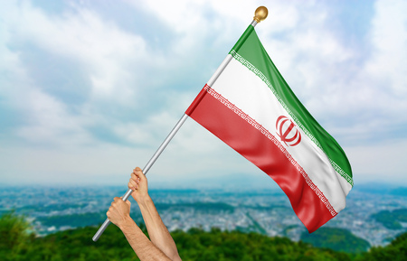 Young mans hands proudly waving the Iran national flag in the sky, part 3D rendering