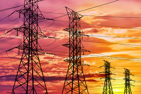 metal grid: High voltage power lines and pylon towers in a bright sunset