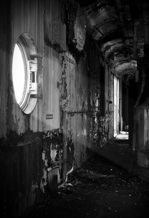 Decayed interior of a spooky abandoned train car with a sunbeam entering through the window