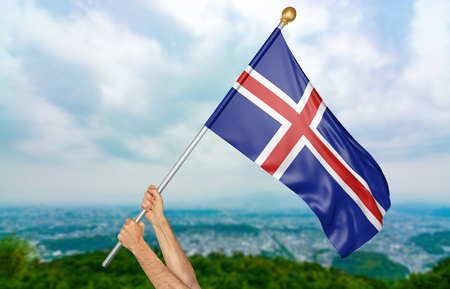 Young mans hands proudly waving the Iceland national flag in the sky, part 3D rendering Stock Photo