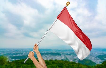 Jonge man handen die trots de nationale vlag van Indonesië in de hemel, deel het 3D teruggeven golven