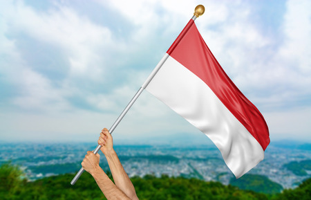 Young mans hands proudly waving the Indonesia national flag in the sky, part 3D rendering