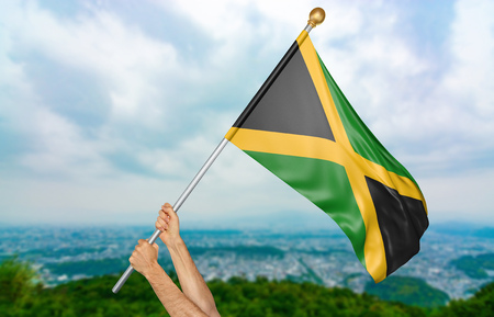activism: Young mans hands proudly waving the Jamaica national flag in the sky, part 3D rendering Stock Photo
