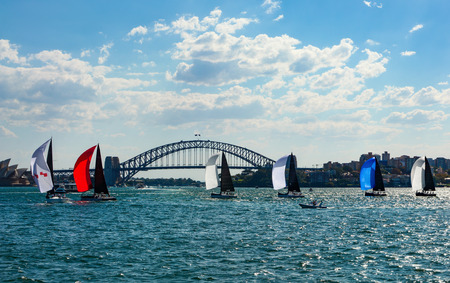 Colorful sailboats with spinnakers crossing Sydney Harbor in front of the iconic bridge in the background Sajtókép