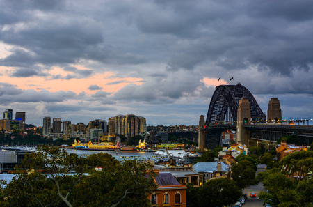 Evening sets over the Sydney Harbour Bridge and lively waterfront in Australias beautiful harbor city Stock Photo