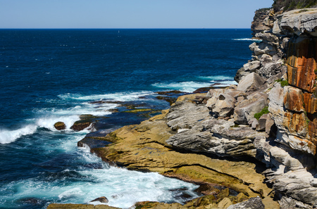Waves crashing against rugged rock coastline at Lady Bay in South Head, NSW, Australia