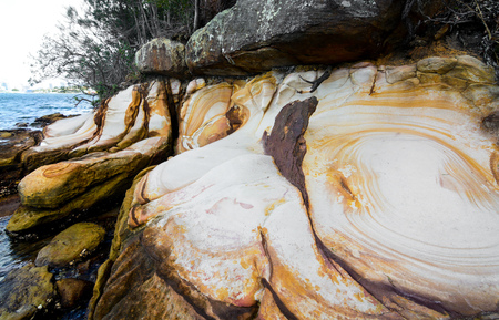 Natural white and yellow-ringed sandstone coast at Berry Island Reserve in Sydney, Australia