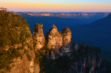 Orange glow of sunset on the peaks of the Three Sisters landmark in the Blue Mountains of Australia