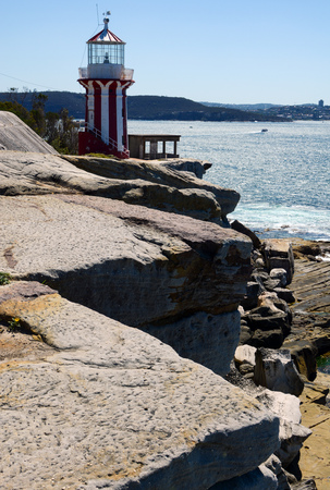 Historic Hornby Lighthouse from 1858 perched on the rocky edge of Lady Bay in South Head, NSW, Australia