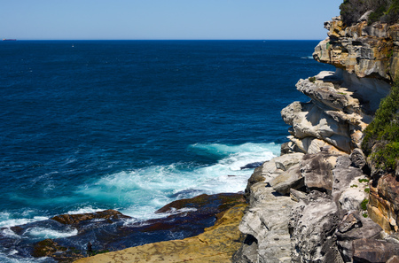 Rocky sandstone cliffs along the jagged coast of Lady Bay in South Head, NSW, Australia