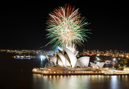 SYDNEY, AUSTRALIA - MARCH 8, 2018 - Colorful mix of orange, green, and white fireworks over the Sydney Opera House