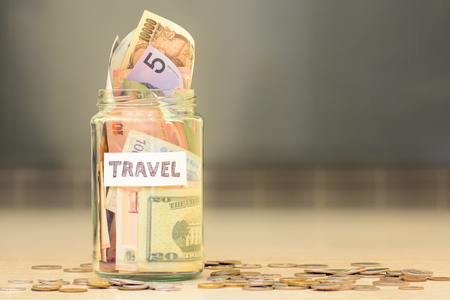 Travel funds jar full of savings with money from different countries