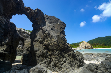 Natural rock arches along the coast at Aharen Beach on Tokashiki Island in Okinawa, Japan