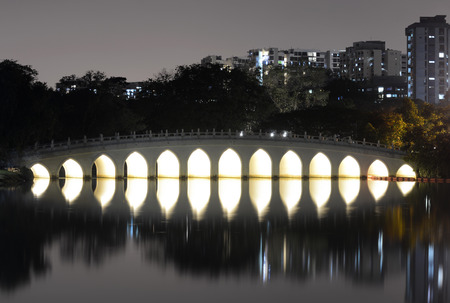 White Rainbow Bridge reflection in water at night in the Chinese Garden, Singapore Redactioneel