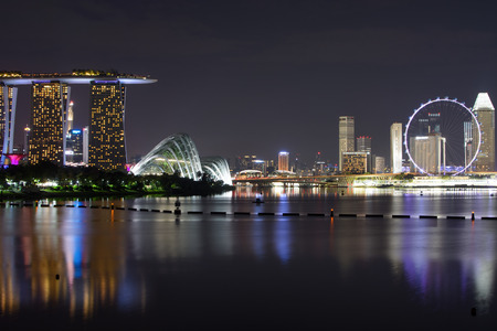 Singapore skyline at night reflecting in the water of Marina Bay