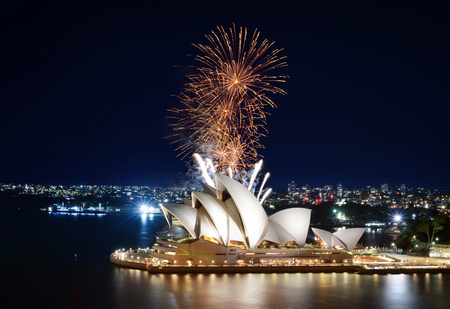 Showers of gold fireworks erupting over the beloved Sydney Opera House at night