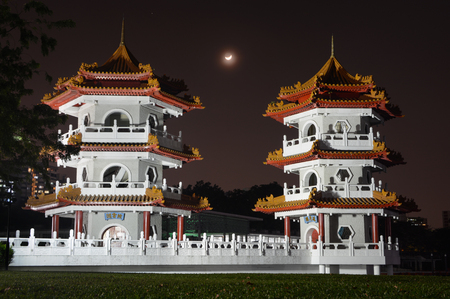 Crescent moon rising in night sky between the Twin Pagodas at the Chinese Garden in Singapore Redactioneel