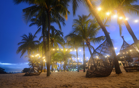 Wicker chairs on a relaxing beachfront at Siloso Beach, Singapore