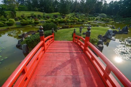 Landscaped grounds and traditional red bridge at the Japanese Garden in Singapore Stockfoto