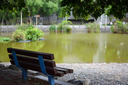 Shaded park bench next to a quiet pond in New Taipei City Imagens