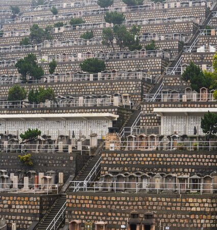 Stairway on a hillside of numerous tombstones in a crowded Hong Kong cemetery