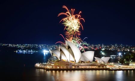 A colorful fireworks display erupts behind the Sydney Opera House after dark