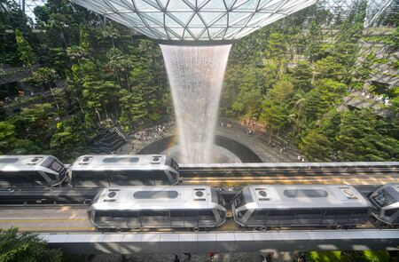 Skytrains traveling past Singapore's Jewel Changi Airport complex and Rain Vortex waterfall