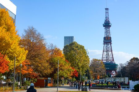 Crowds enjoy sunshine on a chilly autumn day in front of the Sapporo TV Tower in Odori Park Foto de archivo