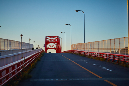 Red color bridge crossing a river in a beautiful morning, Japan. 免版税图像 - 126052287