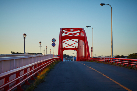 Red color bridge crossing a river in a beautiful morning, Japan. 免版税图像 - 126052445