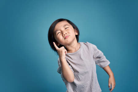 Beautiful asian little kid show wonder, imagine, think, or hesitate. Empty space in studio shot isolated on colorful blue background. Education concept for school.