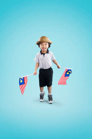 Excited asian little kid holding Malaysia flag. Celebration for national day. Empty space in studio shot isolated on colorful background. Education concept for school.