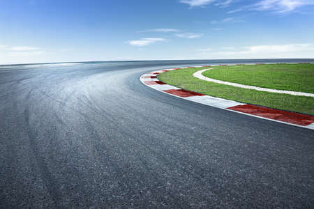 Asphalt race track with dramatic turning curve corner.