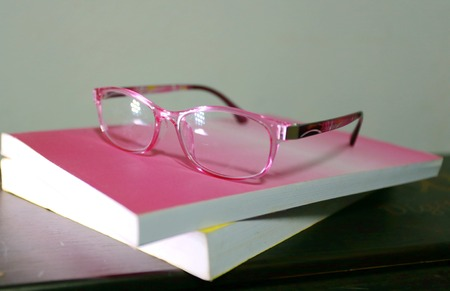 printed matter: The  eye glasses is on the pink and yellow books. Stock Photo