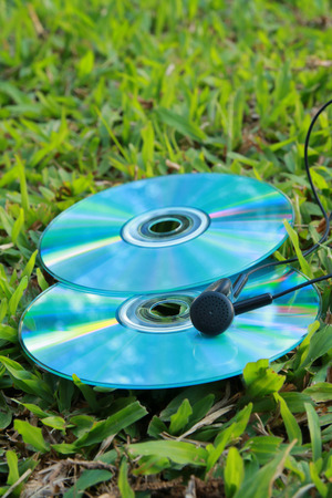 earphone: There are compact disc and earphone on the grassland.