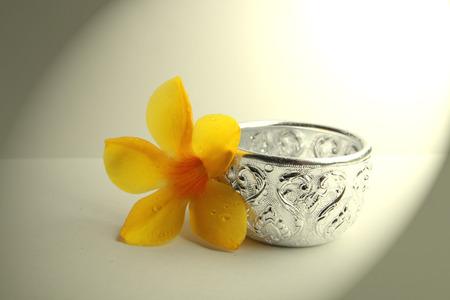 allamanda와 흰색 배경에 작은 은색 그릇.