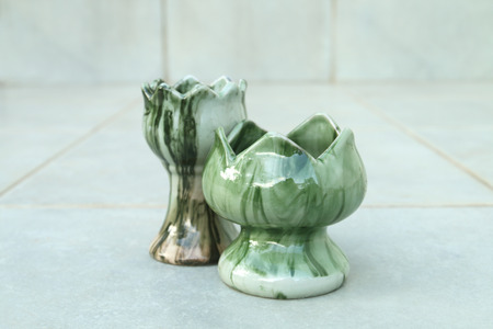 Two of ceramic candlestick on the floor.
