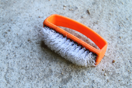 old plastic brush which have the orange handle.