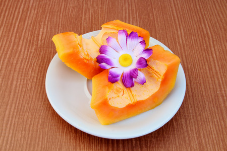 papaya flower: Papaya slice in white plate and decorate with artificial flower.