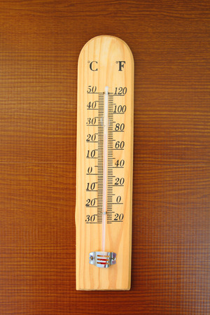 disign: thermometer stick with wooden disign on wooden background