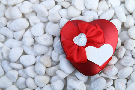red pebble: red fancy heart is on the white pebble Stock Photo