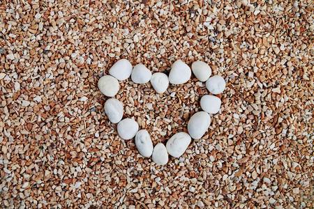 crush on: white pebbles are arrange in shape heart on the crush stone
