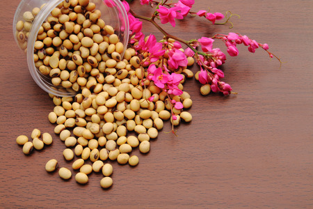 soy beans are pouring on the wooden floor and decorate with pink flower
