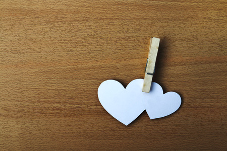 paper pin: two white paper heart are pinch by clip on wooden background