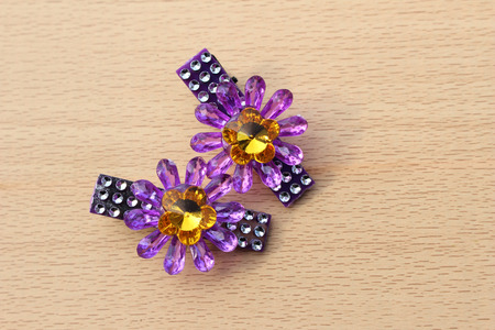 hairpin: Pair of purple plastic  flower hairpin on wooden backgroud Stock Photo