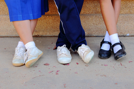 three pairs of student legs which have several uniform in same action Stock Photo