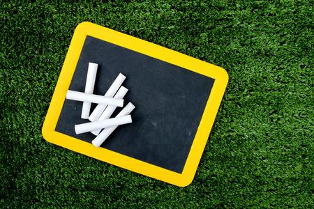 turf pile: used plastic blackboard and pile of white chalk on turf